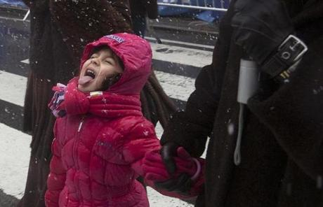 A girl tried to catch snowflakes as she made her way through Times Square.