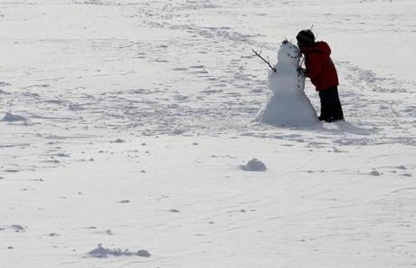A boy built a snowman in Somerville, Mass. following an overnight snow storm.