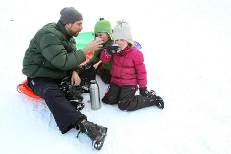 SIP AND SLIDE: John, Bodhi, and Trinity Churchill take a cocoa break after sledding at the Newton Centre Playground 0n December 31.
