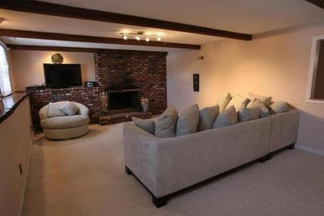 The finished basement includes a second family room with a brick fireplace and exposed beam ceiling.