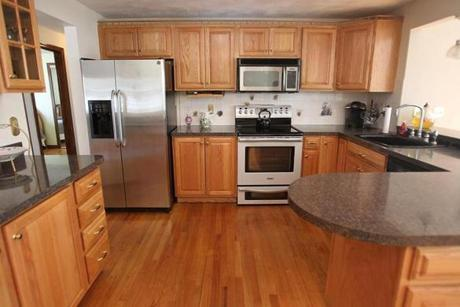 The kitchen has has glass-faced oak cabinets, dark counters, and stainless steel appliances.