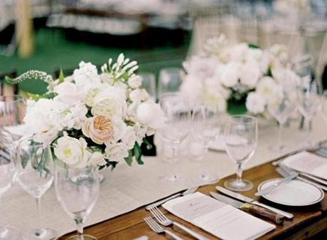 Farm tables at the reception were adorned with centerpieces kept low and full.