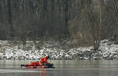 Firefighters worked to rescue a deer trapped on the thin ice on the Cambridge Reservoir in Waltham.