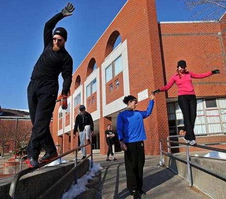 Daniel Abraham, Cristian Lopez, David Kovin, Parkour Generations Americas instructor Blake Evitt, and Rachel Kelly practiced walking across a narrow railing outside of the Somerville High School and the Somerville Library during a class called Boston Weekend Wakeup.