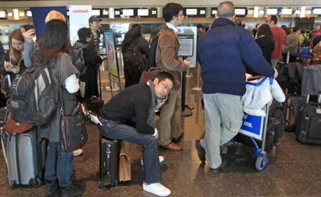 Koji Shinozaki (seated) spoke on the phone while waiting to check in for his Japan Airlines flight to Tokyo. The flight would be canceled after the plane caught fire shortly after landing at Logan on a flight from Tokyo.