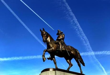 Contrails from jets formed lines in the sky above the statue of George Washington on the Boston Public Garden.