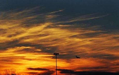 An airplane headed for a landing at Hanscom Field under a colorful winter sunset.