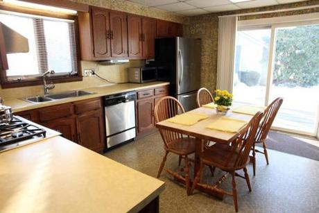 The kitchen,while functional, could stand to lose its flowered wallpaper, linoleum flooring, and weathered cabinets.