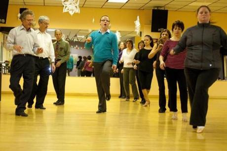 Dance instructor Petr Dubovsky (center), a native of the Czech Republic, leads his class through a series of steps at the Savaria Dance Studio in Norwood.