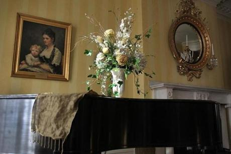 The parlor features a piano and fresh flowers. The painting is on loan from the Massachusetts Historical Society.