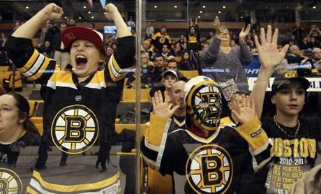 From left: Mika Bauk, Brayden Dalton, and Seth Rosczewski cheered on the Boston Bruins during their first practice at TD Garden since the NHL lockout ended.