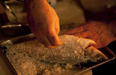 Caruso applied salt to the branzino fish before placing it in the oven.