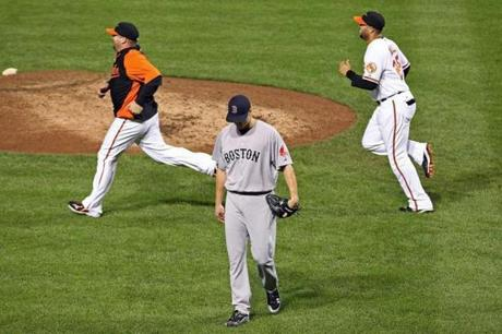 Sox closer Jonathan Papelbon walked off the field as the Orioles rushed to celebrate following thier victory.