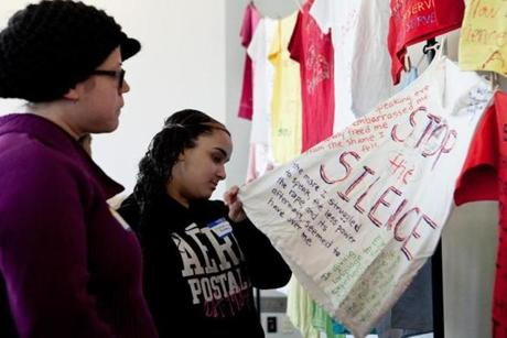 Lisa Moris (left) and Veronica Rivera read T-shirts from the Clothesline Project, a vehicle for women affected by violence to express their emotions by decorating a shirt.