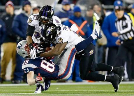Wes Welker catches a pass despite tough coverage by Bernard Pollard and Corey Graham of the Ravens.