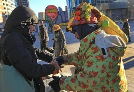 BOSTON MA.01/24/13: FROZEN FRUIT... wearing a fruit hat, Costas Katemis ( cq) selling his fruit near South station to a customer. JUST C O L D…with an arctic blast…Boston was 2 degrees in the morning with a -17 degrees wind chill factor. ( David L Ryan/Globe Staff Photo ) SECTION: METRO TOPIC stand alone photo