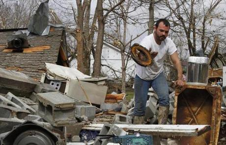 Justin Chandler searched through debris of his brother-in-law's shop after a storm ripped through Coble, Tenn.