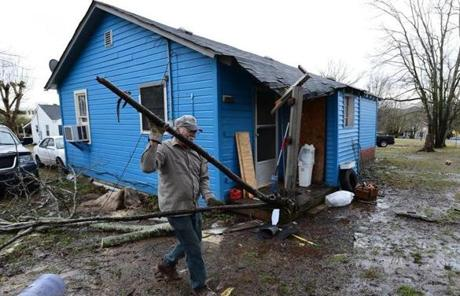 Thomas Ivey carried section of a tree he cut up after it was blown over in Ashland City, Tenn.