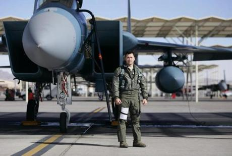 Mayjor Scott Snider stood near his F-15 fighter jet at Nellis Air Force Base in Nevada. In training he plays the enemy target, replicating what a foe might do.