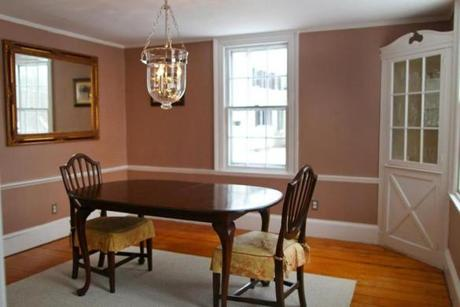 The dining room has a built-in china cabinet, planked flooring, and a period appropriate chandelier.