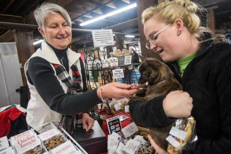 Kathy Varney (left) of Puppy Luv, gives one of her treats to Briana Auclair's  dog Gizmo at the Easton Winter Farmers Market at Simpson Spring in Easton.