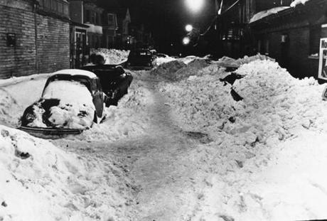 Deep snow covered cars and the street in Egleston Square.
