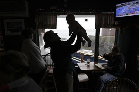 It was a relaxed atmosphere among patrons and workers at The Barnacle, with waitress Bethany Cook sharing a moment of play with Quinn Nevins as the storm approached.