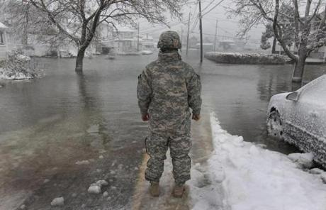 PFC Juan Jimens with the 11 82nd National Guard looked over a flooded Turner Road in Scituate.