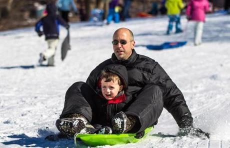 Thomas Appleton and his 4-year-old son, Nalu, rode a sled down a small hill in Boston Common.