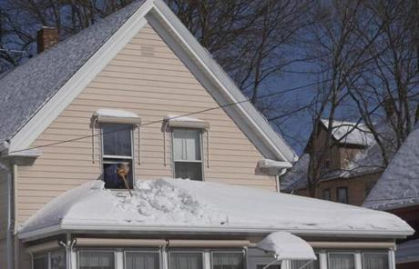 Leo Verrochi leaned out a window to clean off the roof of his front porch in Quincy.