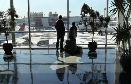 After seeing a family member off, the Villamil family of Boston paused to watch planes out a window at Logan Airport.