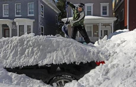 William Curdo got a roof's-eye view of the snowfall as he cleaned off his car on  M Street in South Boston.