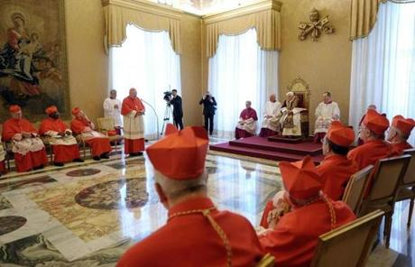 Pope Benedict XVI, sitting on the throne at (center right), met with  Vatican cardinals on Monday.
