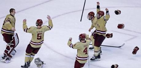 Sticks and gloves flew as the BC Eagles rushed to goalie Parker Milner (left) following their 6-3 victory over Northeastern University in the championship game of the Beanpot Tournament at the TD Garden.