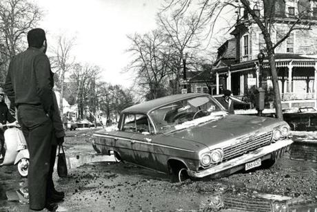 November 16, 1967: This car was half-buried about a foot deep in this pothole in front of 516 Warren Street in Boston.
