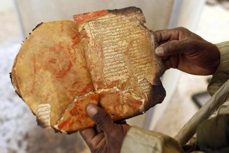 A museum guard displayed a burnt ancient manuscript at the Ahmed Baba Institute last month.