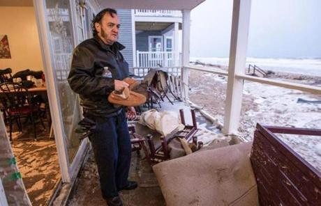 Edward Bemis inspected the damage to his Salisbury home caused by a wave.