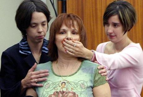 Sisters Jessica (L) and Kristen Garvey (R) restrain their mother, Dina A. DeMaio, from speaking out after reading a victim impact statement about her daughter Dina A. DeMaio, who died in The Station nightclub fire during the sentencing of nightclub owners Michael and Jeffrey Derderian at the Kent County Courthouse in Warwick, Rhode Island September 29, 2006. A hundred people died in the Station Nightclub Fire which was sparked by pyrotechnics that ignited the foam during a concert by Great White on Feb. 20, 2003. REUTERS/Bob Breidenbach/Pool (UNITED STATES)