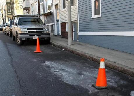 The snow was gone on School Street in Charlestown, but cones used as space savers stayed.