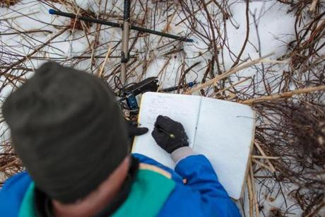 After finding a turtle buried under the ice and snow, Bryan Windmiller marked down its GPS coordinates in a book.