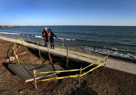 Passersby walk past storm erosion damage to the sea wall undermining the sidewalk on Long Beach in Rockport.