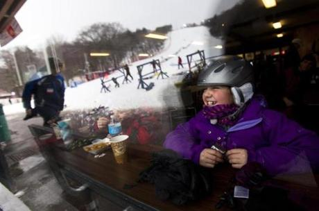 Allie Gefteas, 10, of Canton, took a break from skiing to warm up with M&Ms and Sprite at Blue Hills Ski Area.