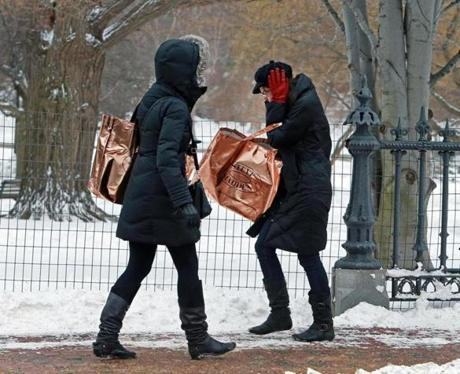2/17/13: Boston, MA: Two pedestrians who were walking together on Arlington Street this afternoon try to stay warm as a strong gust of wind buffets them, with the one at left turning around and walking backwards, while the one at right covers her ears to stay warm and also to make sure her hat doesn't fly off. section: metro topic: weather feature (Jim Davis/Globe Staff)