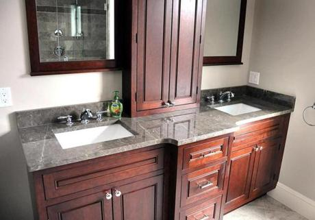The master bath has a cherry double vanity and a large, all-body shower with glass doors and a seat.