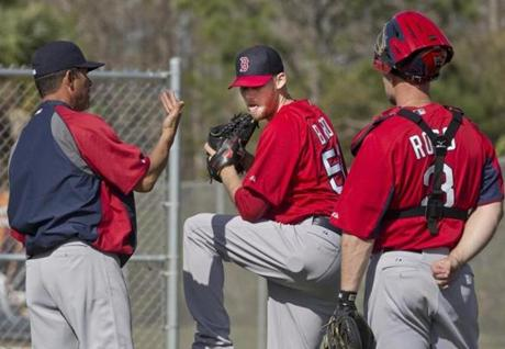 Red Sox pitching coach Juan Nieves worked with reliever Daniel Bard with catcher David Ross looking on.