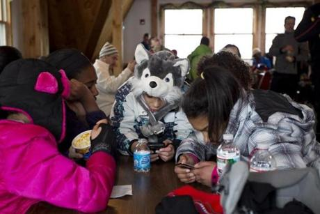 Maya Schwinn-Clanton, 10, in the husky hat, hangs out with friends during a break at the Valley Lodge.