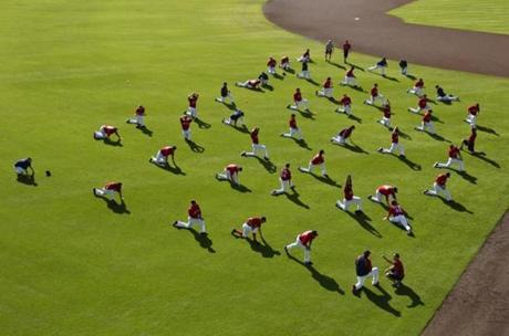 Boston Red Sox players stretched in the outfield before the start of their exhibition season opener at JetBlue Park in Fort Myers.