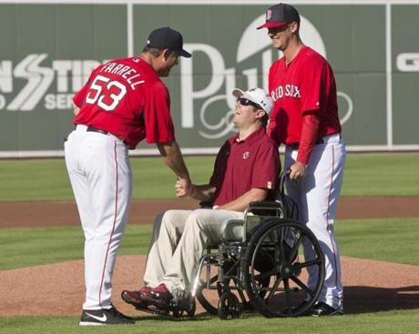 Red Sox manager John Farrell greeted ex-BC player Peter Frates, stricken with ALS, before a scrimmage with the Eagles. Escorting Frates is his former BC teammate and current Red Sox pitcher Terry Doyle.