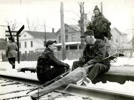 February 26, 1938 / Proving skiing is for all ages, William H. Smythe, age 70 of Allston, chatted with Harry Muzzy, 17 of Worcester, as they waited for the train after a day of skiing at Mount Greylock's Thunderbolt Trail in Adams, Mass.