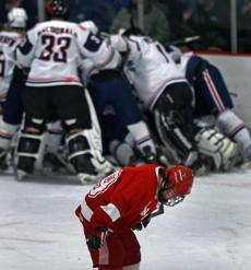 Hingham's Stephen Hughes (front) skated away as Central Catholic celebrated an overtime win. Hingham saw a 3-0 lead disappear as Central won 4-3 in the overtime period in Super 8 hockey action at Stoneham Arena.
